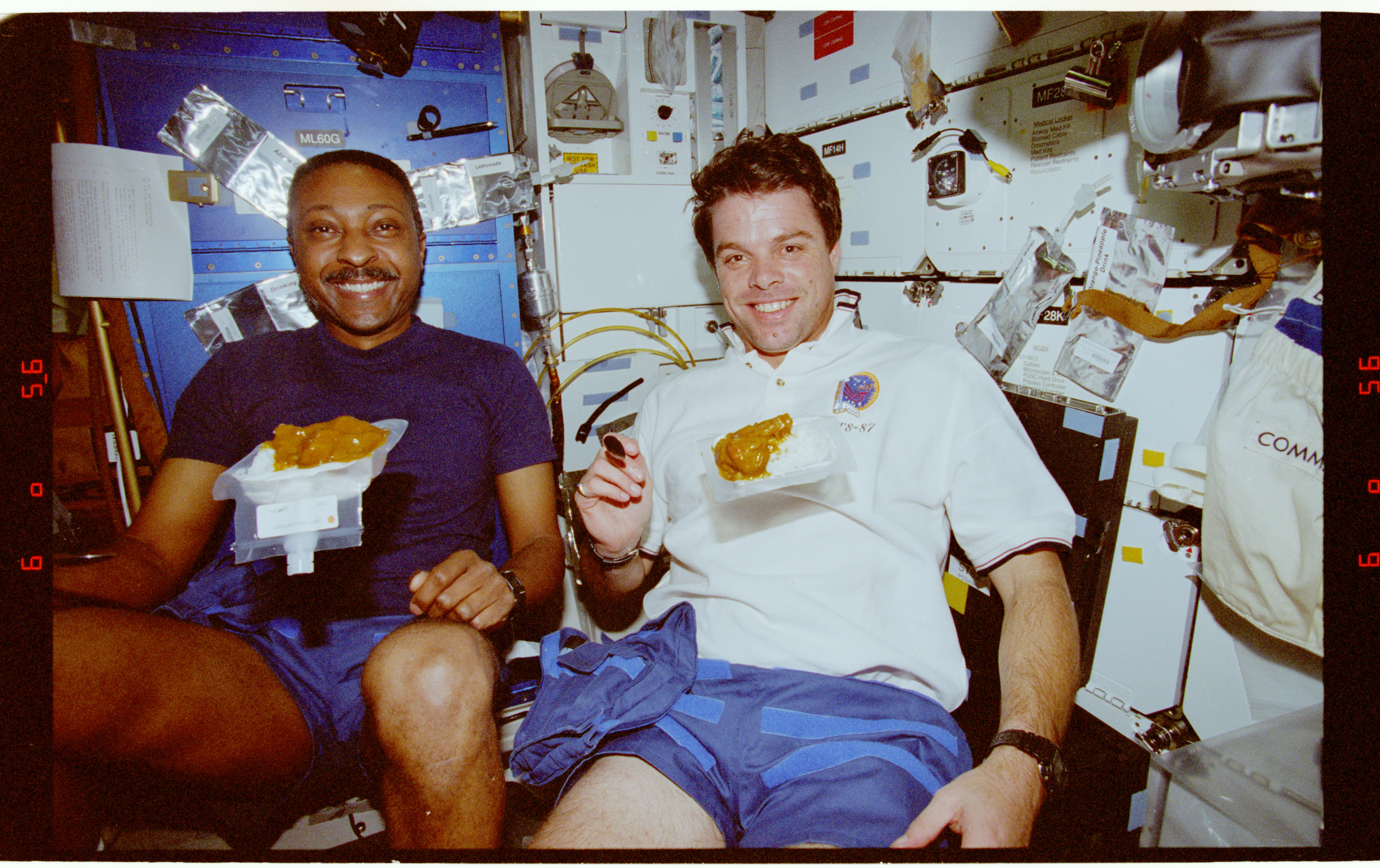 STS087-375-018 - STS-087 - Crewmembers share a meal in the middeck