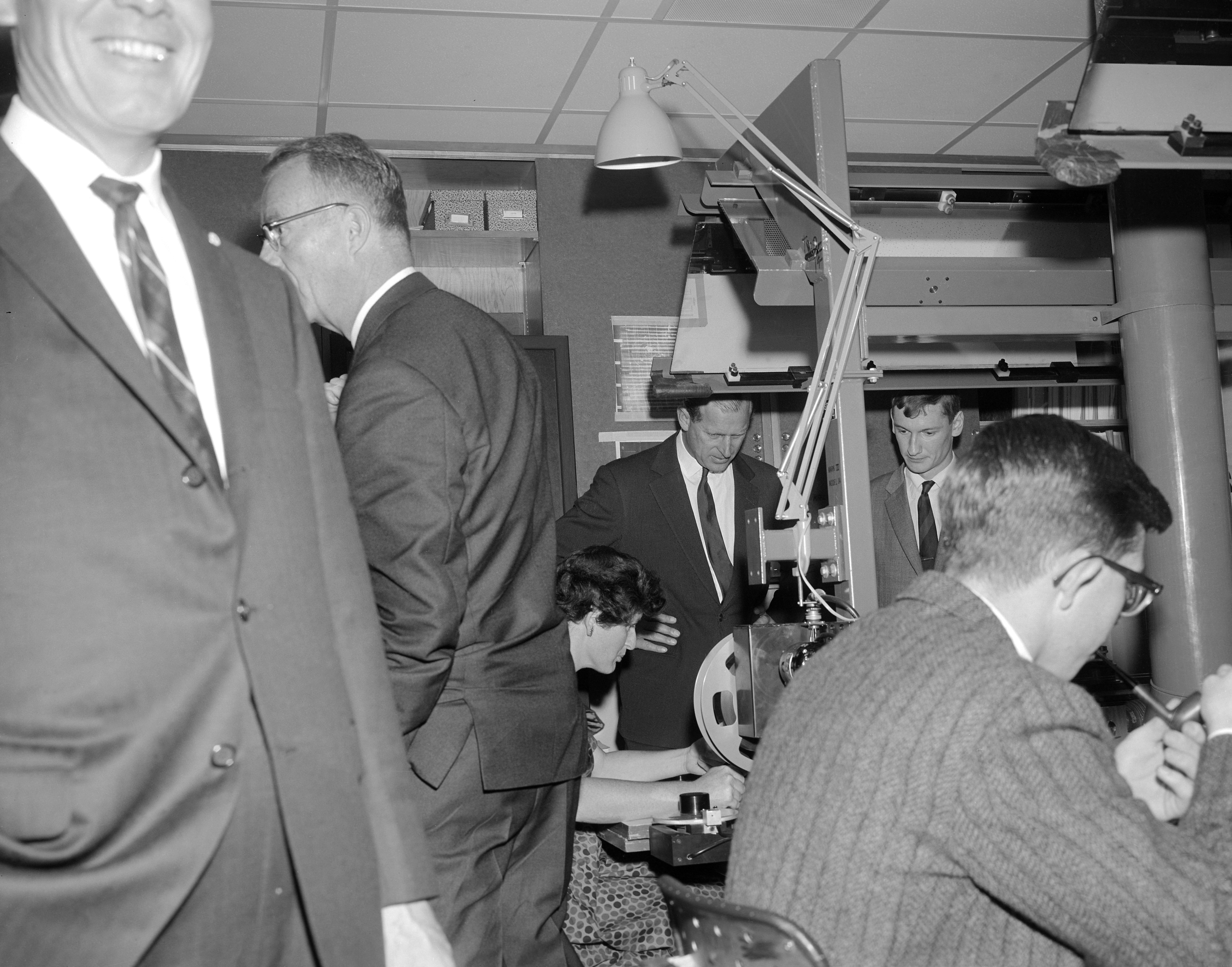 Fellow Brits Margaret Alston (seated, L.) and Peter Davey (standing, R.), guest scientists in the Alvarez Group, show His Royal Highness, Prince Philip of England, how bubble chamber films are scanned and measured in the group's data reduction center in Building 50. Photograph taken November 14, 1962. Morgue 1962-57(P-16). [Photograph by: George Kawaga]